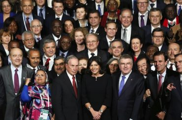 Mayor of Paris Anne Hidalgo (C), former mayor of New York Michael Bloomberg (C-L),  President of the International Olympic Committee (IOC) Thomas Bach (C-R) and local elected pose for a family photo at the Paris townhall during a summit on climat as part of the World Climate Change Conference 2015 (COP21) on December 3, 2015 in Paris.    More than 150 world leaders are meeting under heightened security, for the 21st Session of the Conference of the Parties to the United Nations Framework Convention on Climate Change COP21/CMP11) from November 30 to December 11. / AFP / PATRICK KOVARIK